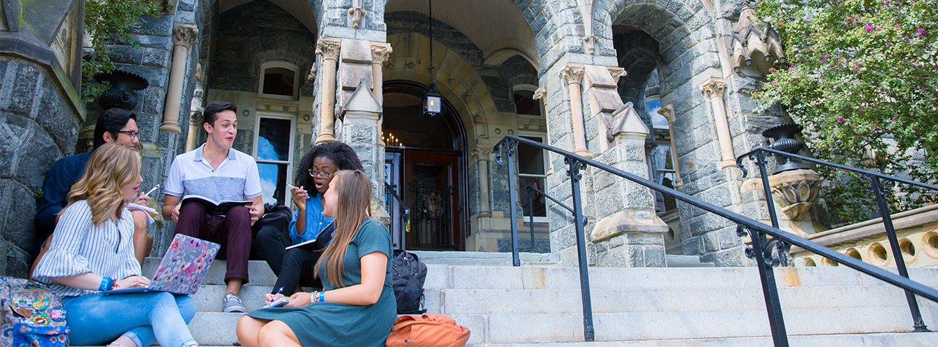 Students sitting down Healy Hall's steps